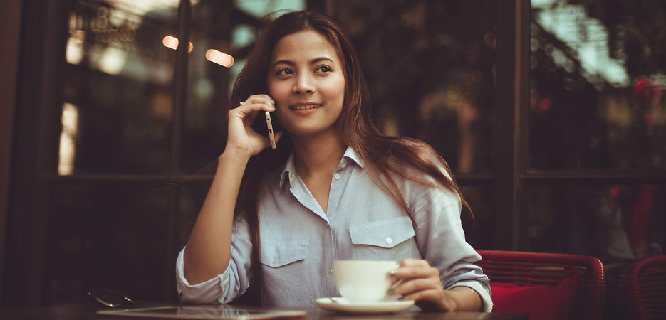 woman making a sales phone call at a table