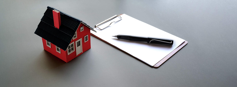 House on a table next to a clipboard