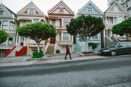 woman walking by victorian style homes
