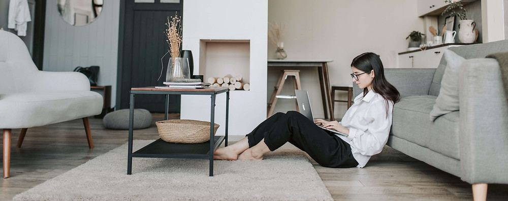 Woman sitting on the floor using her laptop.
