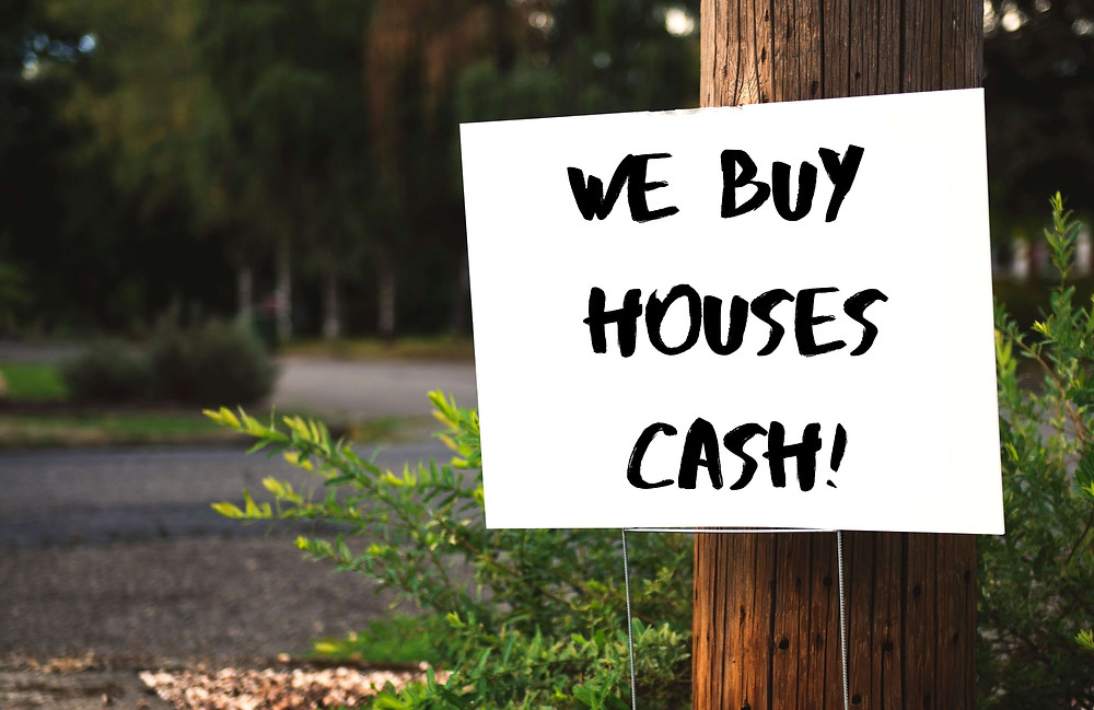 A We Buy Houses sign stuck in the ground in front of a pole