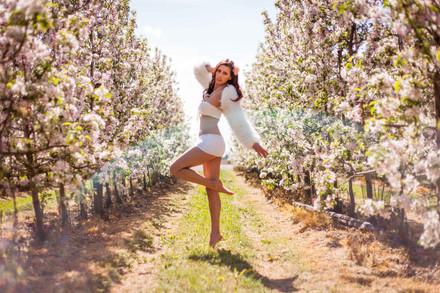 séance photo de Cecile dans un champs de pommier au printemps