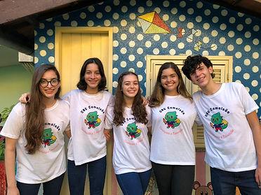 A equipe está em pe, todos sorrindo, no corpo a blusa da ONG e uma calça jeans. Da esquerda para a direita: uma menina de cabelos castanhos longos, de óculos; outra menina, esta de cabelo castanho escuro curto; em sequência, outra moça, esta de cabelo castanho claro; mais uma menina, esta de cabelo loiro; por último, um menino de cabelo ondulado curto.