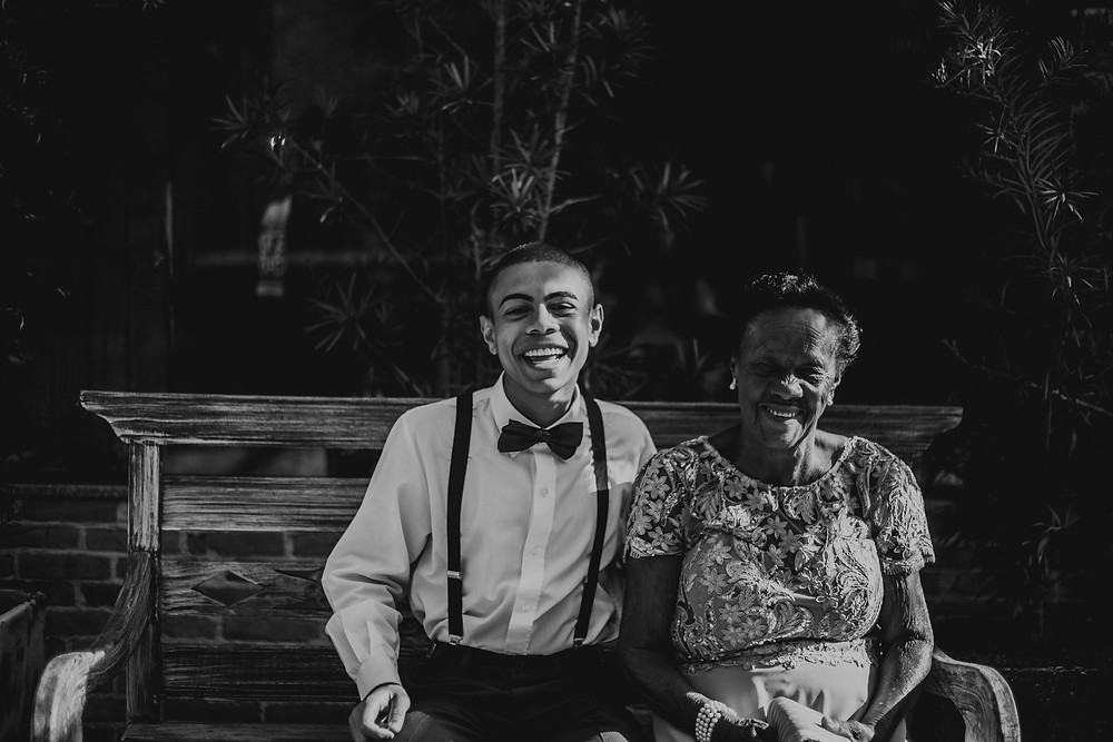 young black man and elderly black woman sit on bench together. smiling