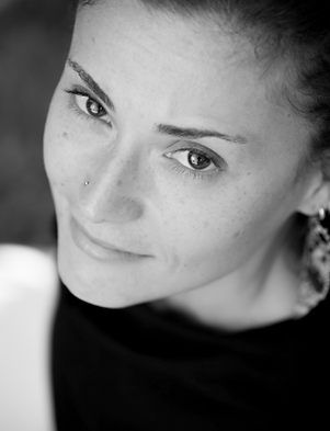 Black and white headshot of Andrea wearing a black shirt and looking up at the camera.