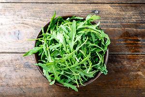 fresh arugula salad in a clay plate on t