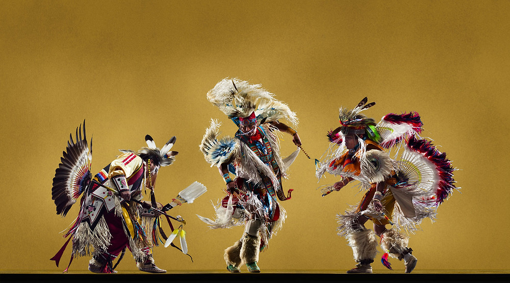 Moccasin-shod Native Americans  dancing, and singing, together in a group.