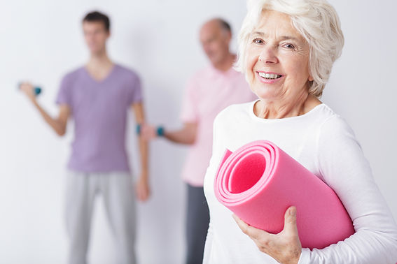 Elderly Woman Exercising At A Gym.