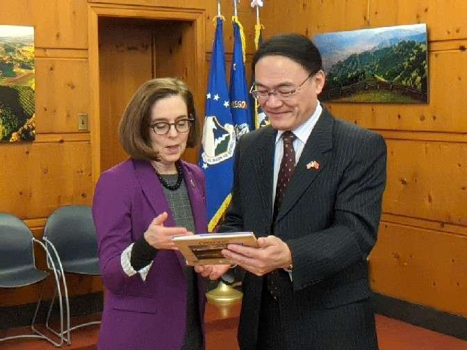 Consul General Wang Donghua presenting Governor Kate Brown with a gift at their February 24 meeting.