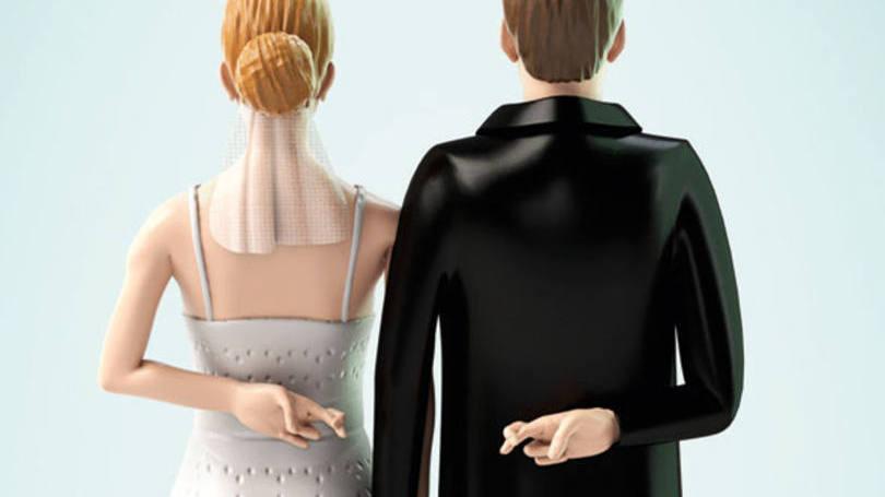 Casal de noivos com os braços para trás e dedos cruzados.
