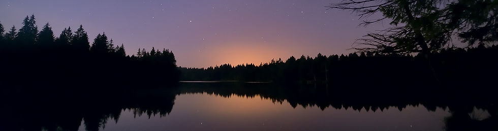 picture of a rising sun in the Jura forest with reflection in a lake