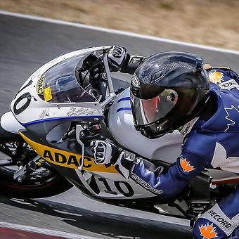 Valentino Herrlich unterwegs mit seinem Motorrad auf der Rennstrecke. Er befindet sich mit seinem ADAC bemarktem Motorrad in Schräglage.