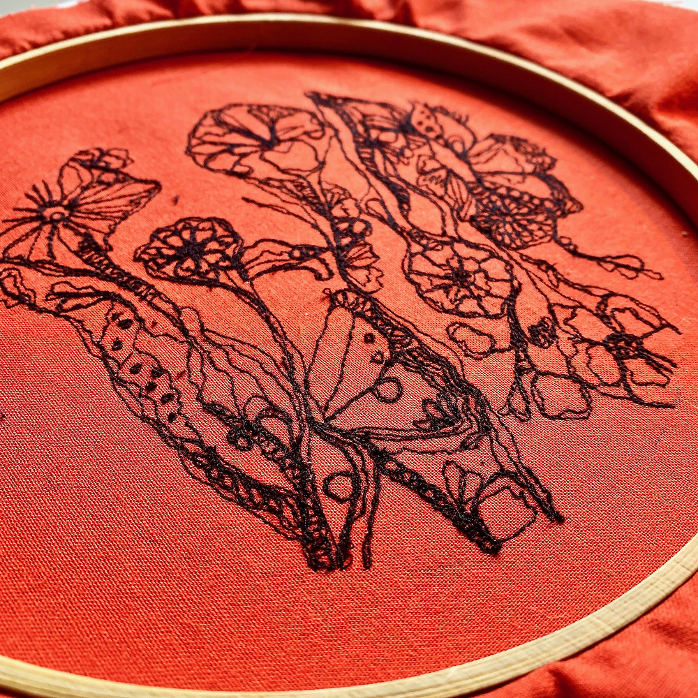 Freehand machine embroidered floral design with black cotton on orange fabric