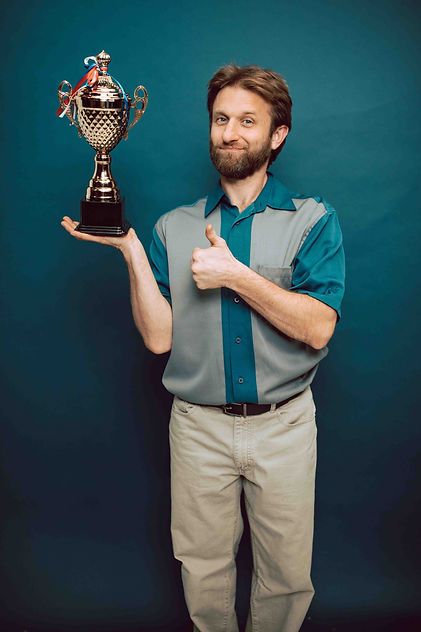man holding trophy thumbs up.jpg