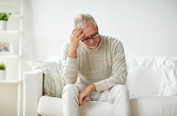 health, pain, stress, old age and people concept - senior man suffering from headache at home