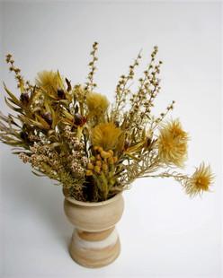 Naturalistic dried floral arrangement in a marbled ceramic vase
