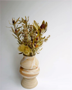 Small dried floral arrangement in marble ceramic vase