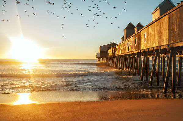 Early morning by the ocean. Wooden old p