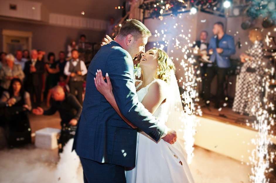Newly married couple dancing on their wedding party with heavy smoke, multicolored lights
