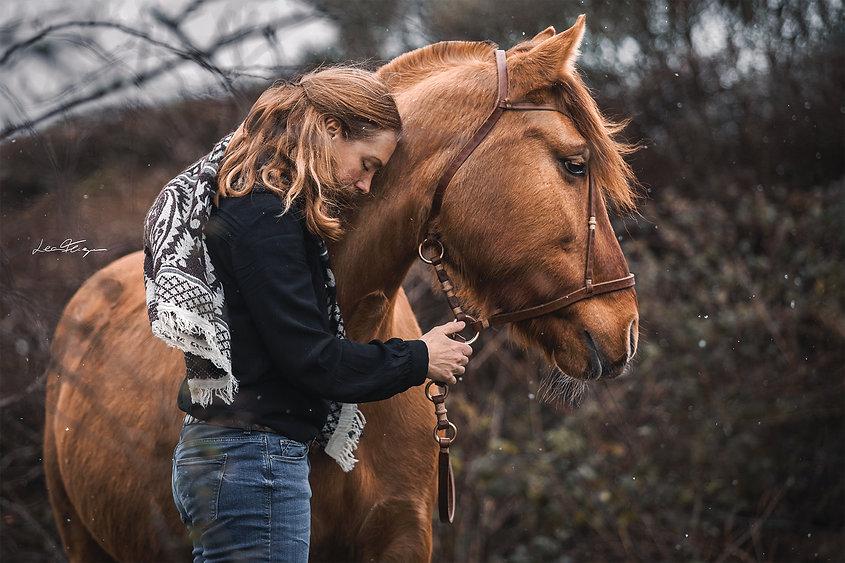 Frau mit Pferd, lehnt ihre Stirn an den Hals des Pferdes, Pferd schaut rechts aus dem Bild heraus, kühle Stimmung und Schneeflocken