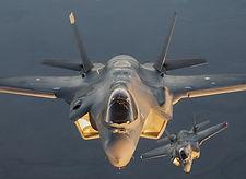 an-f-35a-flies-next-to-an-f-25b-during-w