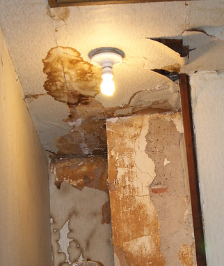Water damage has caused damage to the ceiling, wall, and even started to erode the plaster around this chimney resulting in a gas leak.