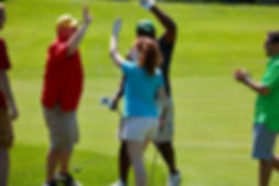 Three golfers high-fiving on a green during Classic for Kids Golf Outing event