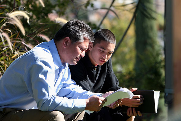Adult man and teenage boy reading together