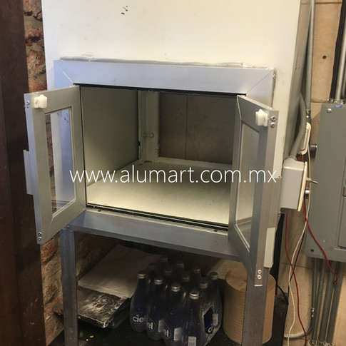 Puerta para elevador de cocina en aluminio natural con cristal en 6mm