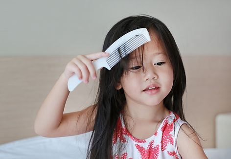Asian little girl combing hair.jpg