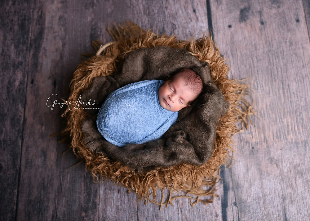 Newborn baby photography is best done when the baby is 5-15 days old. Seems early doesn't it? Newborn portraits are done that early since they sleep most of the time, are still used to being all curled up like when they were in the womb and this makes it easier to create all those lovely, peaceful photographs of your little baby. As your baby gets older, they like to move around a lot while they are awake, making all those jerky little karate moves that can make them hard to photograph. They also like to stretch out more, enjoying their new found freedom, changing ever so fast from the moment when they were born.