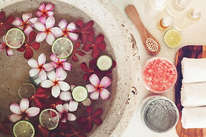 Foot bath in bowl with lime and tropical flowers, spa pedicure treatment, top view.jpg