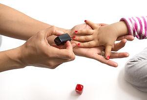 Mother Applying Nail Polish To Her Little Girl.jpg