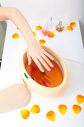Female Hand And Orange Paraffin Wax Bowl. Woman In Beauty Salon.jpg