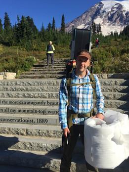 Geoff hiking a unit to Pan Point, Mt. Rainier