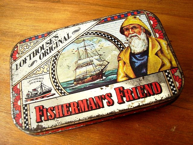 Middle image of a sailing wooden ship with white sails surrounded by seagulls. Ship faces to the right towards a bearded fisherman in yellow fishing clothes that takes up all the space on the right side, pun intended. The words Lofthouse's original flies across the top of the tin box while the words Fishermen's Friend boxes at the bottom third of the tin box. (Source: pinterest)