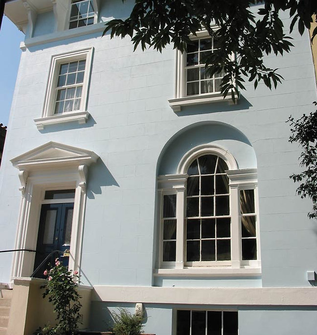 Front of a blue house with arched window