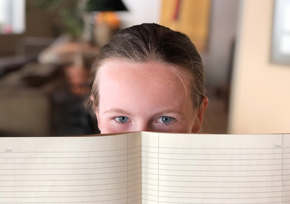 Girl smiling with eyes holding an open college ruled notebook