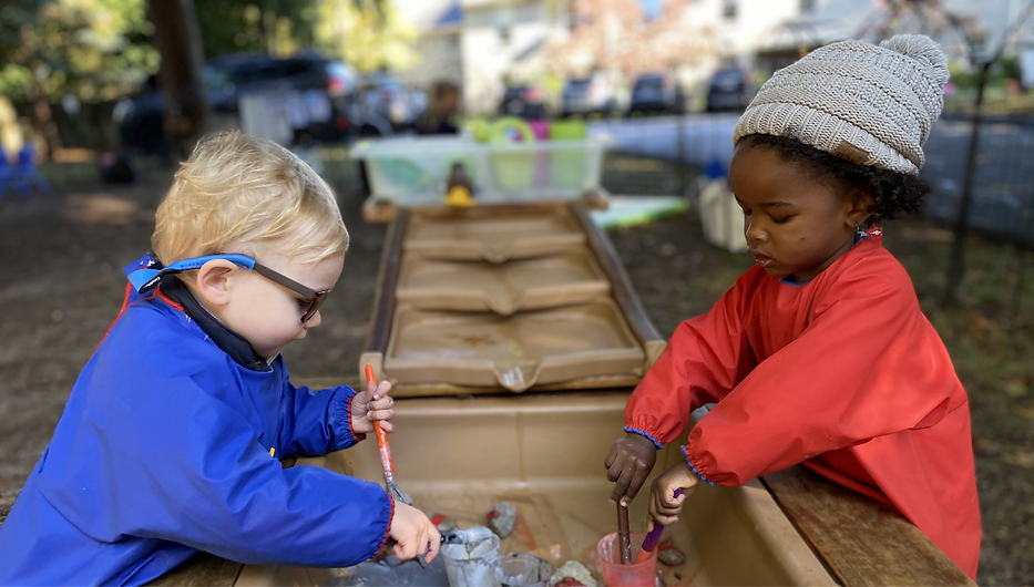 Girl and boy playing at water table