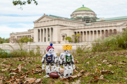 """For the classic NFL rivalry game, ROBOTIS-MINIs changed into their Bears and Packers gear (complete with a custom """"cheese head""""). (Photo: ©Kasumi Chow, Museum of Science and Industry, Chicago)"""