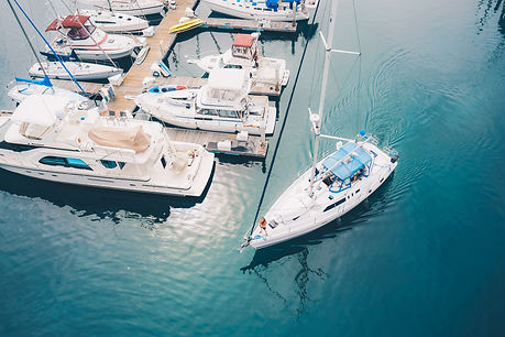 white-boat-leaving-marina-docks-sailing-