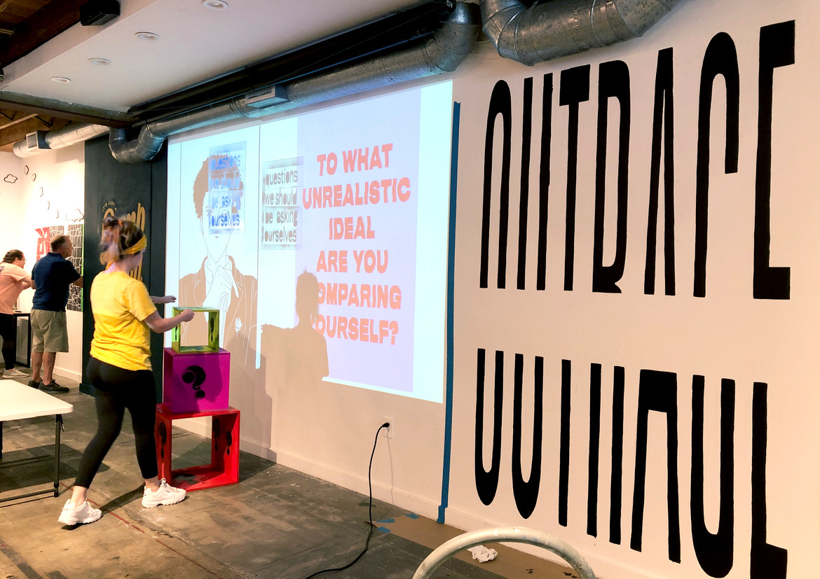 """Outrageous: in progress. The word """"outrage"""" was painted onto the wall, a projector was used for precision. A shelf and posters were then placed over top of the paint to make the wordmark difficult to read. This was done in order to underscore the idea that outrage clouds mature conversation, making it difficult to understand and deliver clear messaging."""