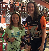 AnnaTheArcher and young girl smile at Bass Pro
