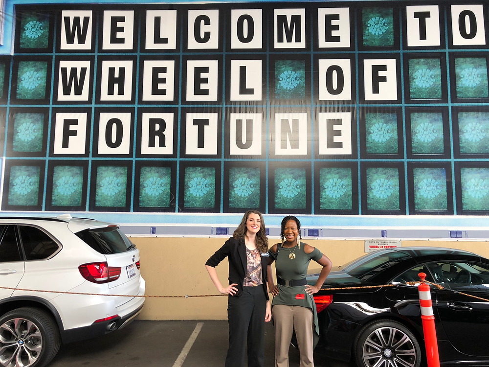 Anna stand in front of Wheel of Fortune sign