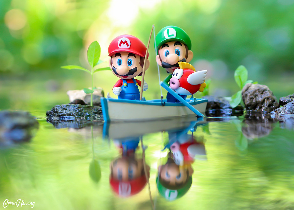 Toy Photography by CuriousHerring of Mario and Luigi Nendoroid from Nintendo Super Mario. Mario is holding a fishing rod and Luigi is holding a cheep cheep fish, both on board a boat sailing across the Mario Sunshine universe.