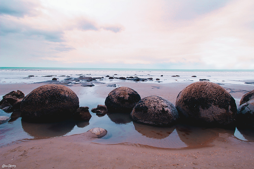 Landscape Photography by CuriousHerring, boulders on the beach looking out across the ocean in New Zealand