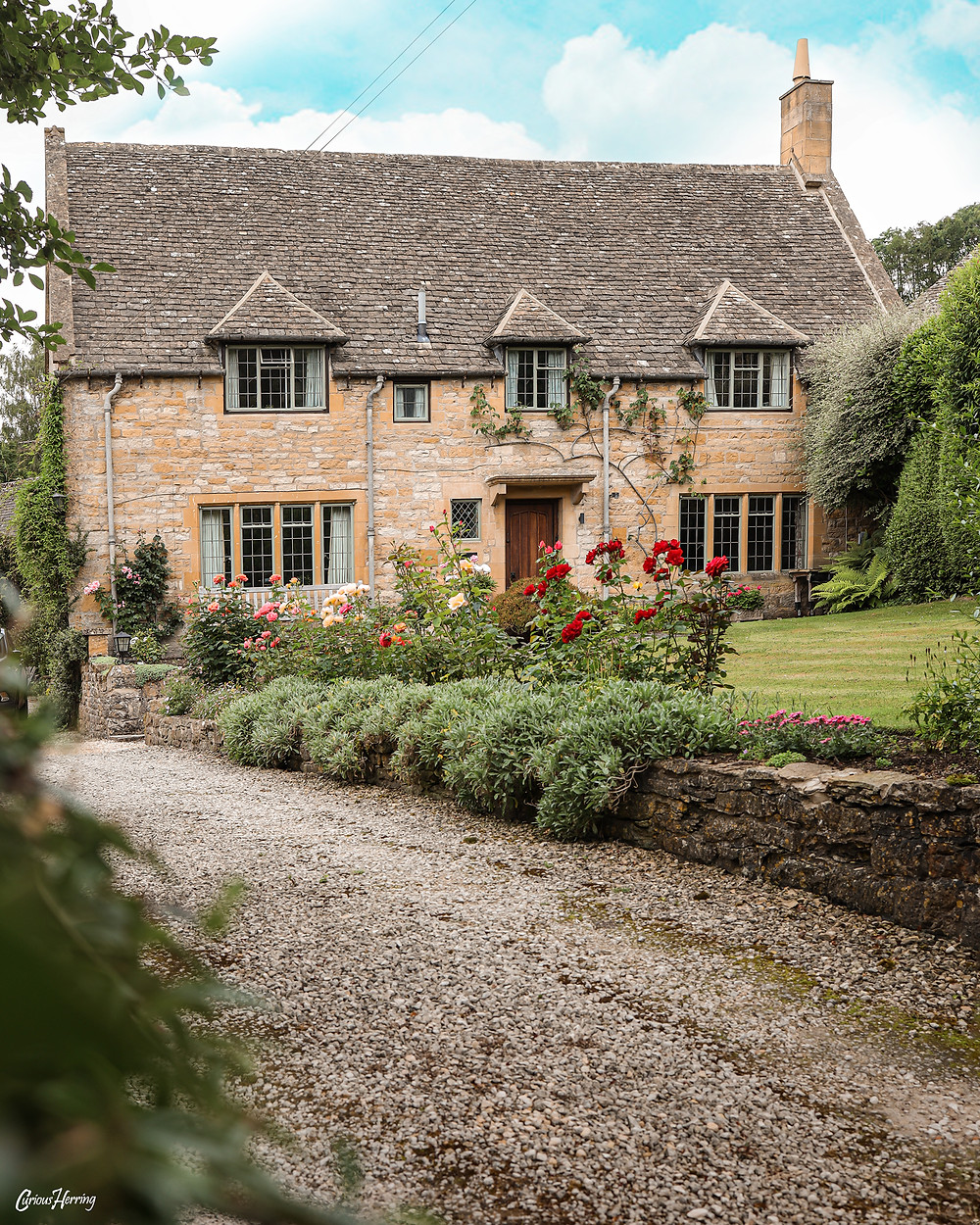 A cottage house surrounded by flowers and vined roses in Snowshill, Cotswolds.