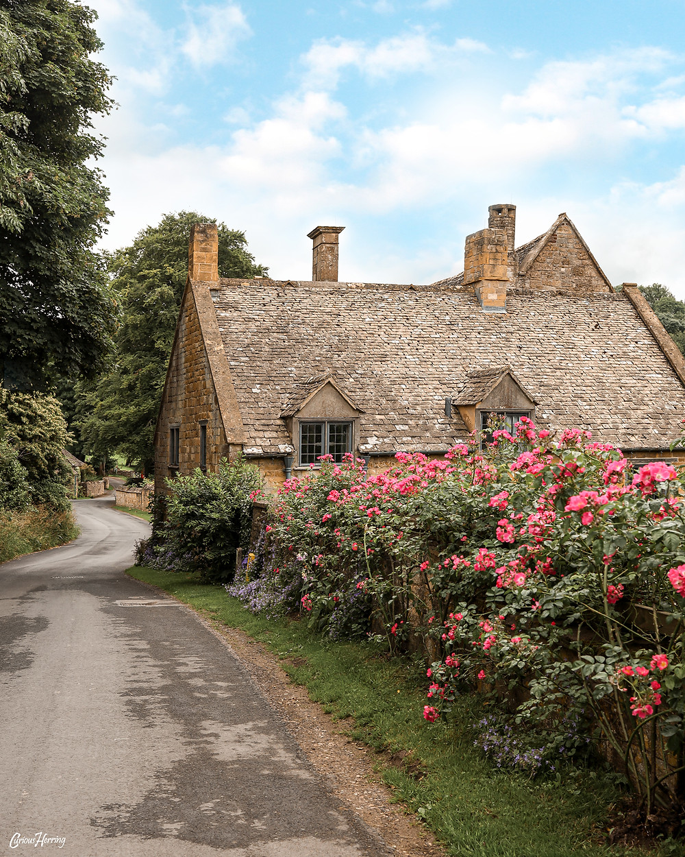 A cobbled street wall covered in wallflowers which surround Snowshill Manor, Cotswolds.