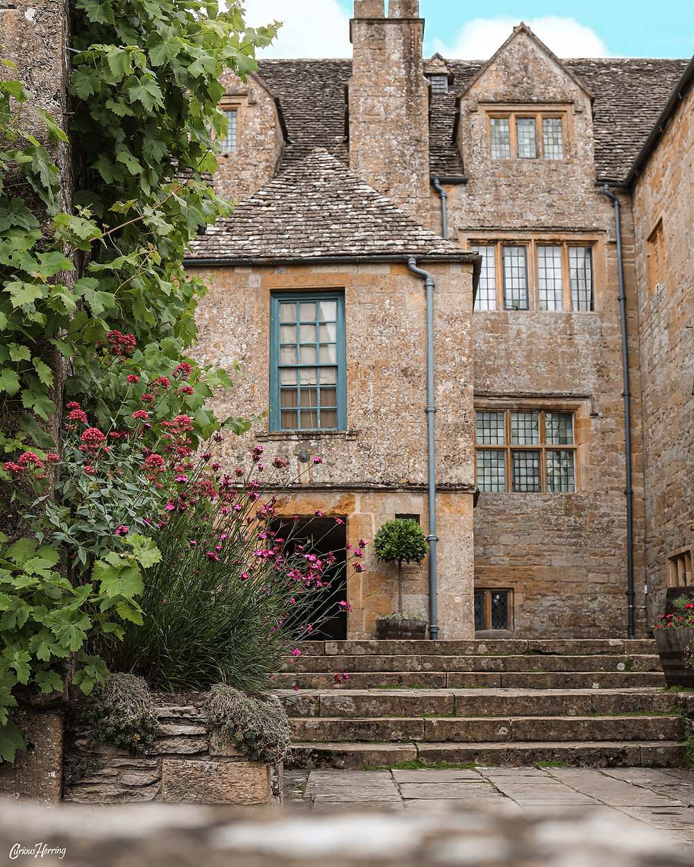 Architecture of Snowshill Manor in the Cotswolds, framed by wild vines and flowers