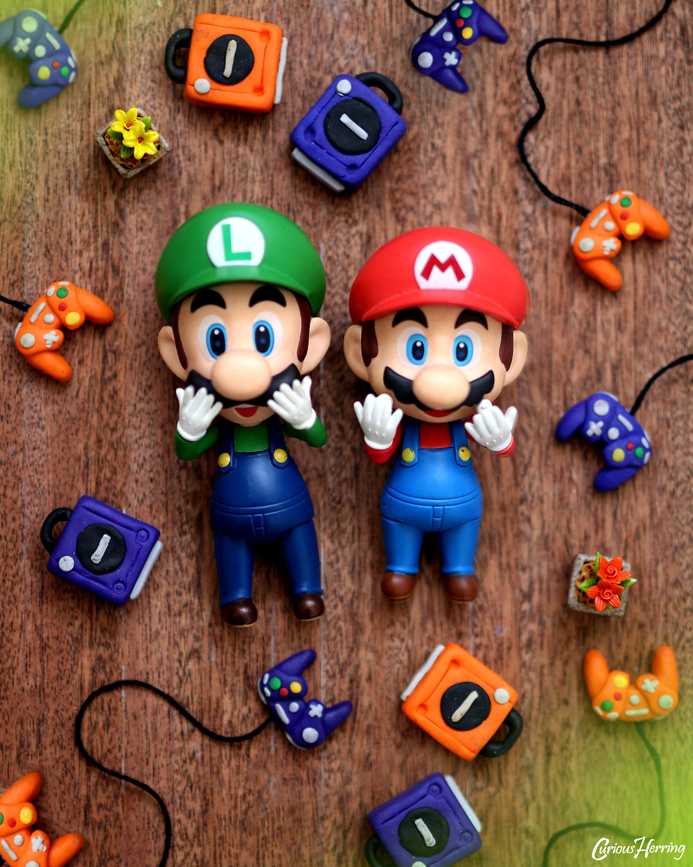 Mario Nendoroid and Luigi Nendoroid with miniature DIY GameCube made out of Fimo. Toy and Nendoroid Photography focusing on Nintendo related figures and games.